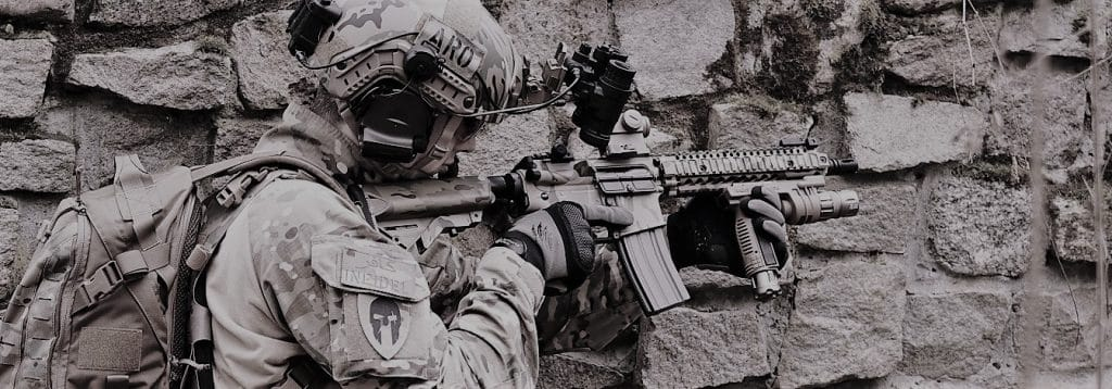 milsim player with airsoft gun prepping for attack