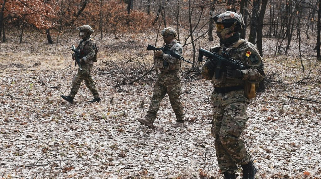 airsoft players patroling forest in milsim operation